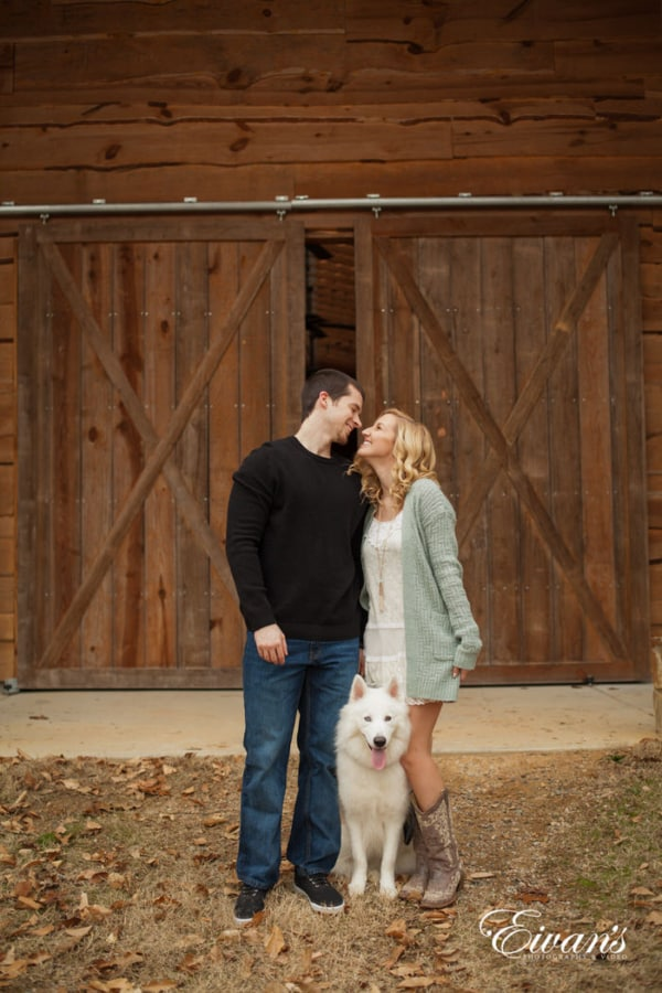 In this photograph, the couple smiles in front of rustic barn doors that are made of natural wood. They are not alone though, they are with their beloved companion and best friend.