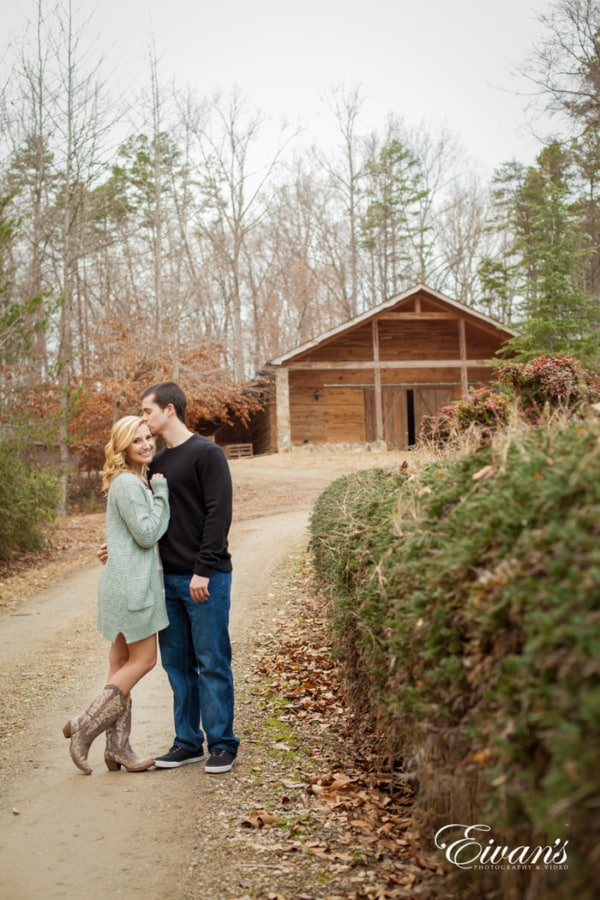 Standing on this beautiful pathway from the rustic barn , the couple embraces one another in the cool fall weather. Their smiles radiating at the idea of forever continuing their lives together.
