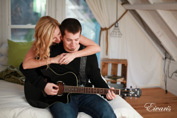 The gorgeous soon-to-be bride holds onto her amazing love of her life while he plays his guitar for her.