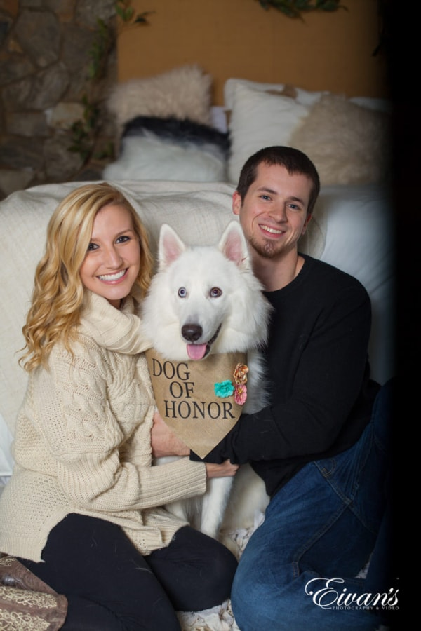 This couple holds onto their beloved dog of honor, simply smiling with all of the joy in the world.