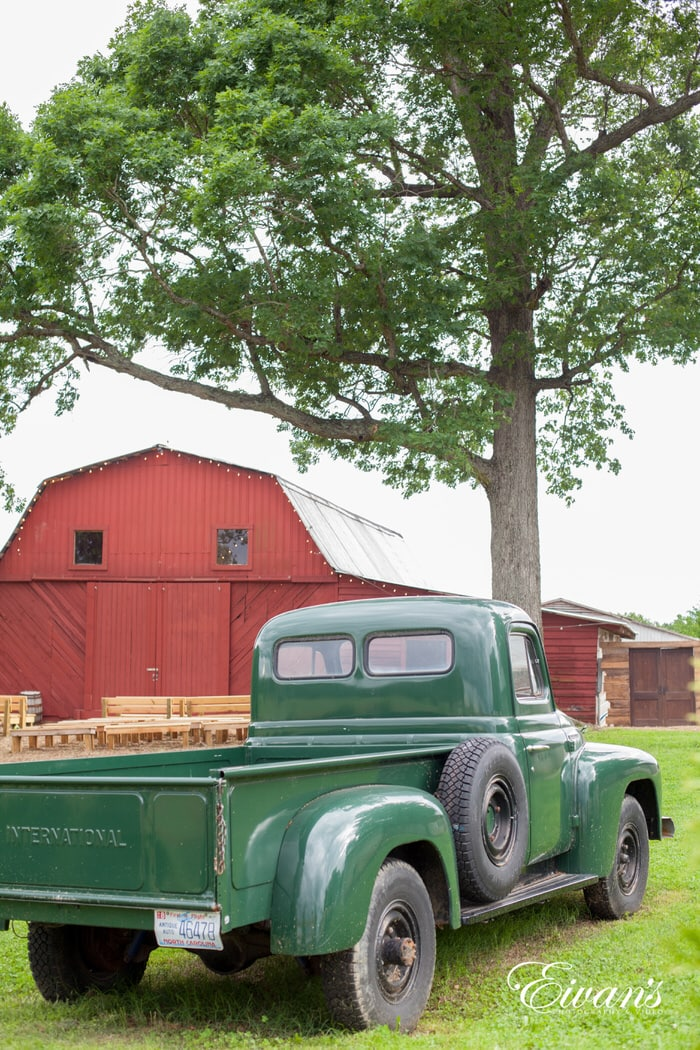 green single cab pickup truck parked beside red wooden house during daytime