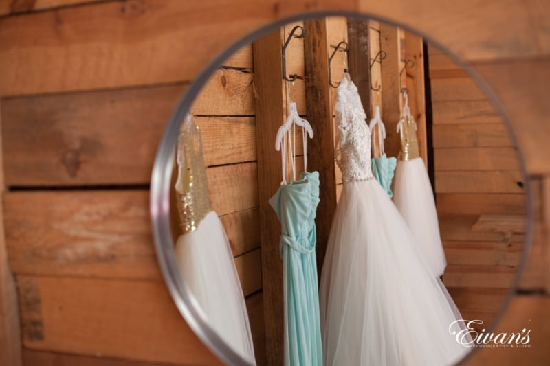 In this mirrored image are the bride's, bridesmaids', and flower girls' dresses. All lovely placed among a rustic wooden wall.