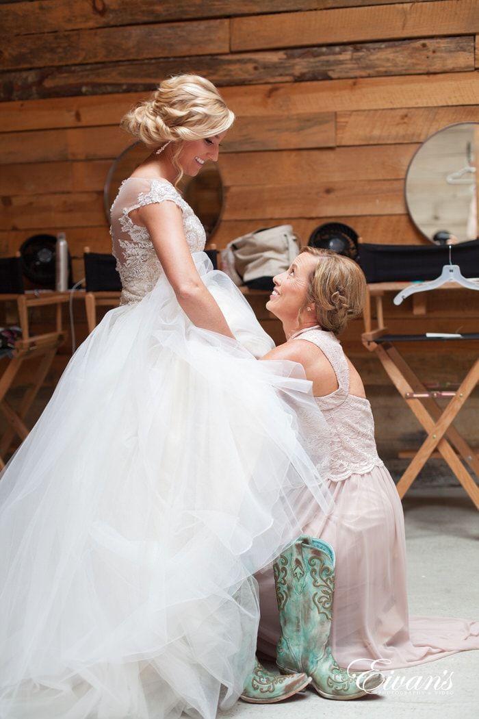 This moment that the bride and her mother spend together is helping slip the bride wear her mint green cowboy boots.