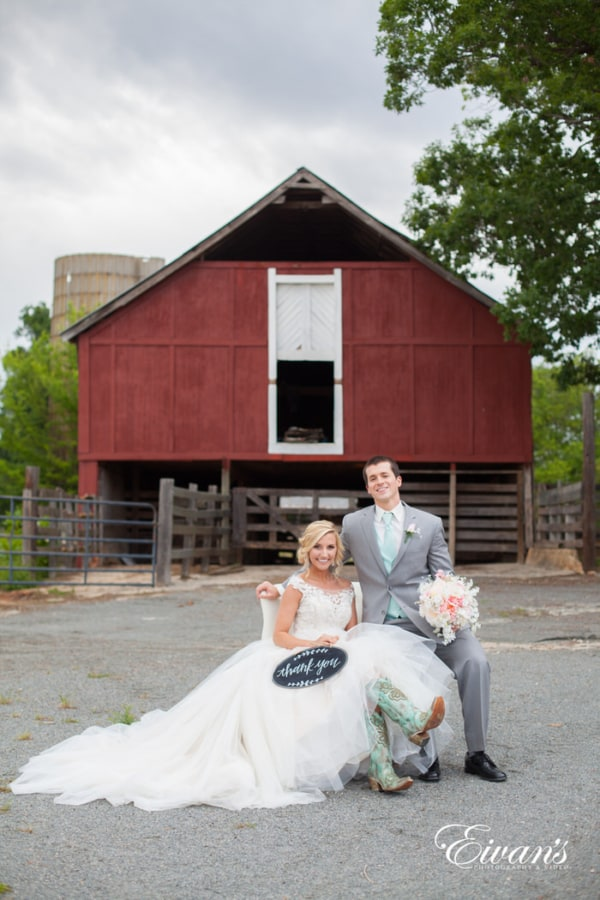 The couple sits together in front of a beautiful and rustic barn celebrating their love together.