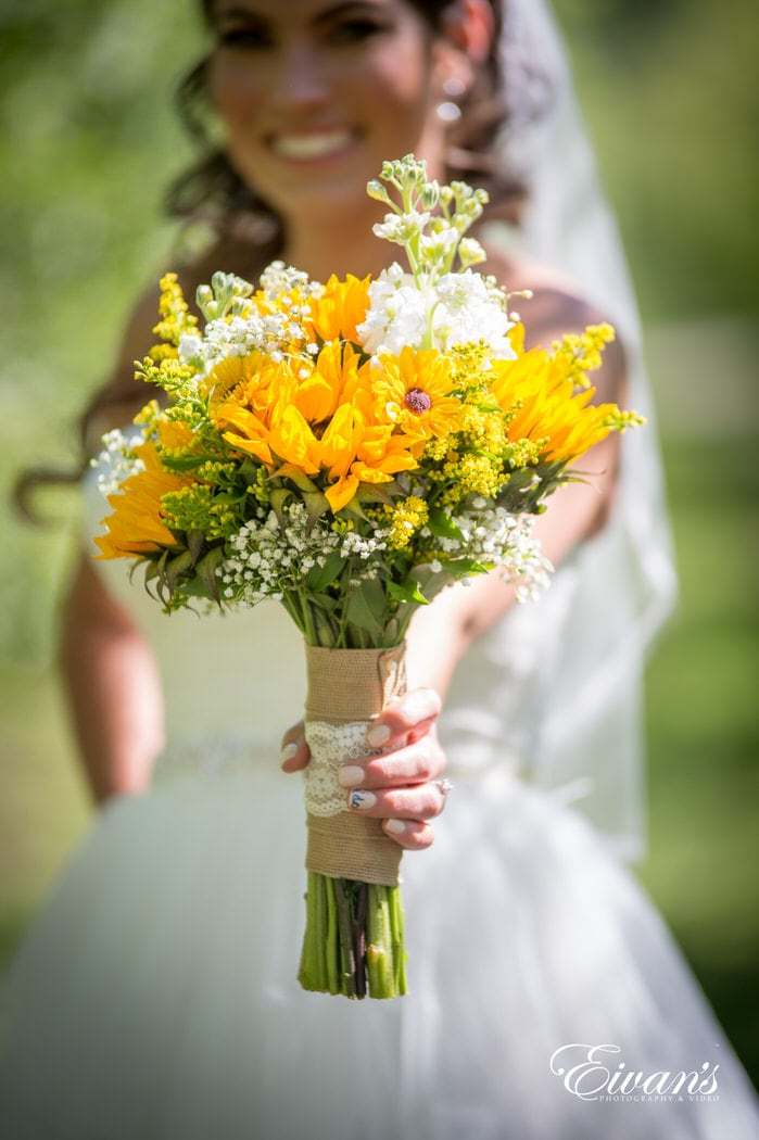 Holding her rustic bouquet made of classic white flowers and vibrant sunflowers.