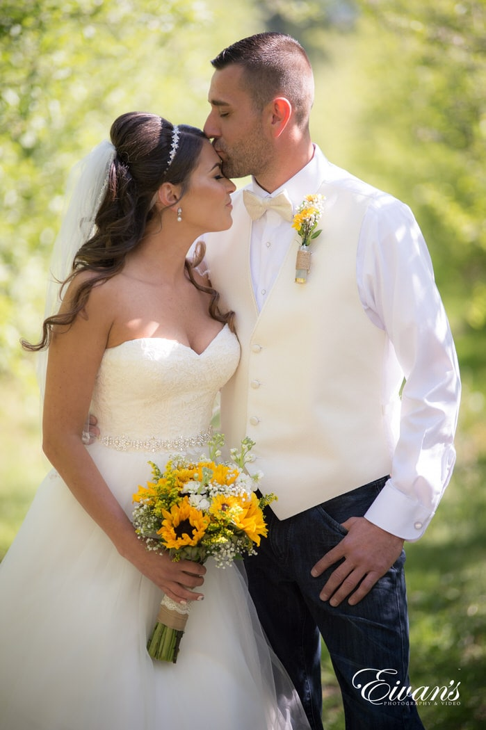 The groom kisses his newly found wife while celebrating their new marriage.