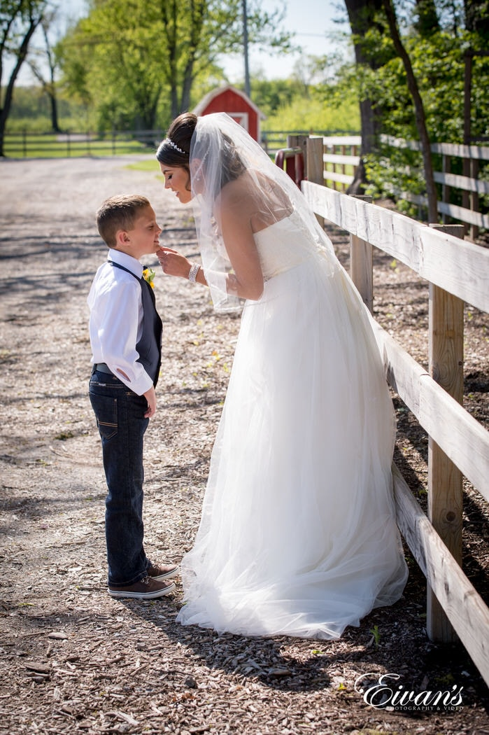 Going to kiss the head of the little ring bearer while standing and leaning on a wood fence enjoying the sun and beautiful weather.