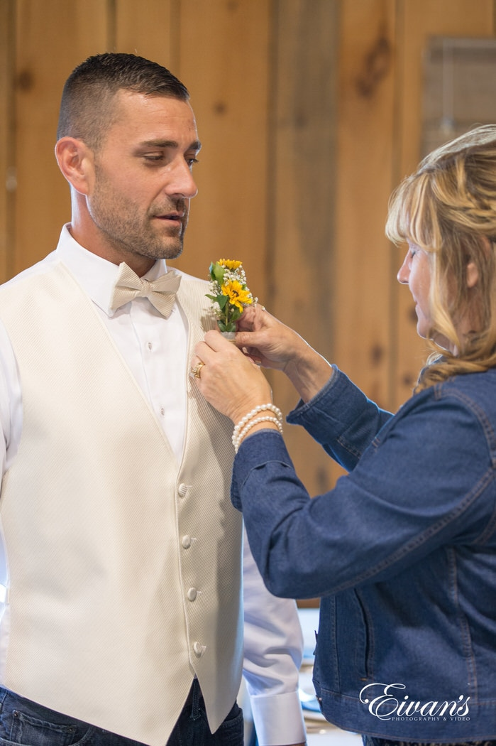 Placing a sunflower boutonniere on her son's and the groom's vest for his more then special day.
