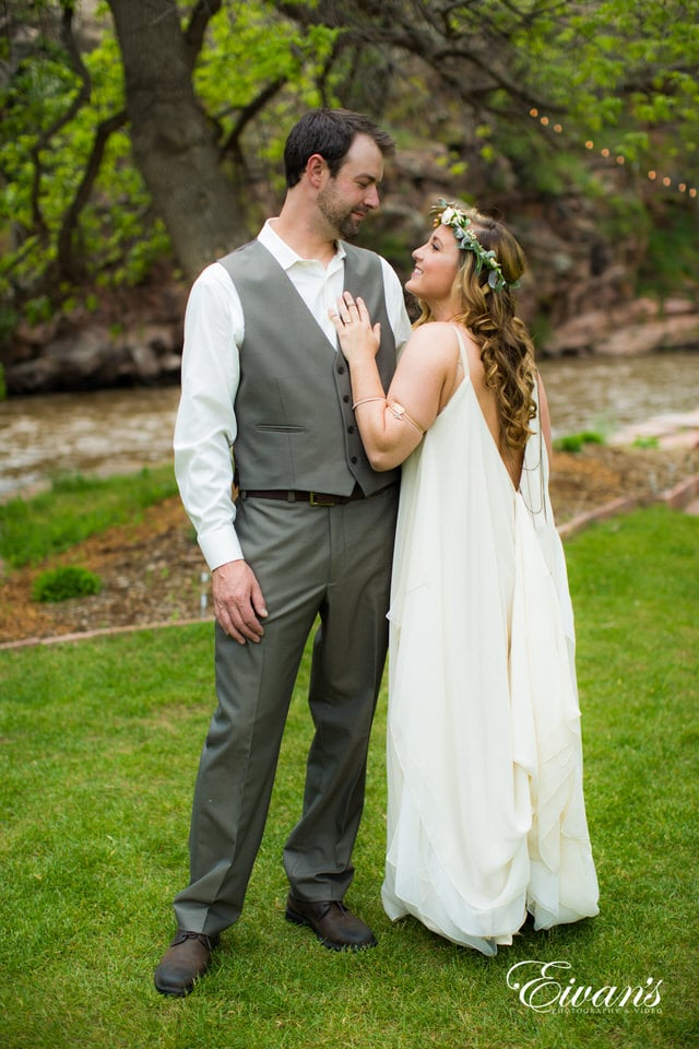 man in gray suit and woman in white wedding dress kissing