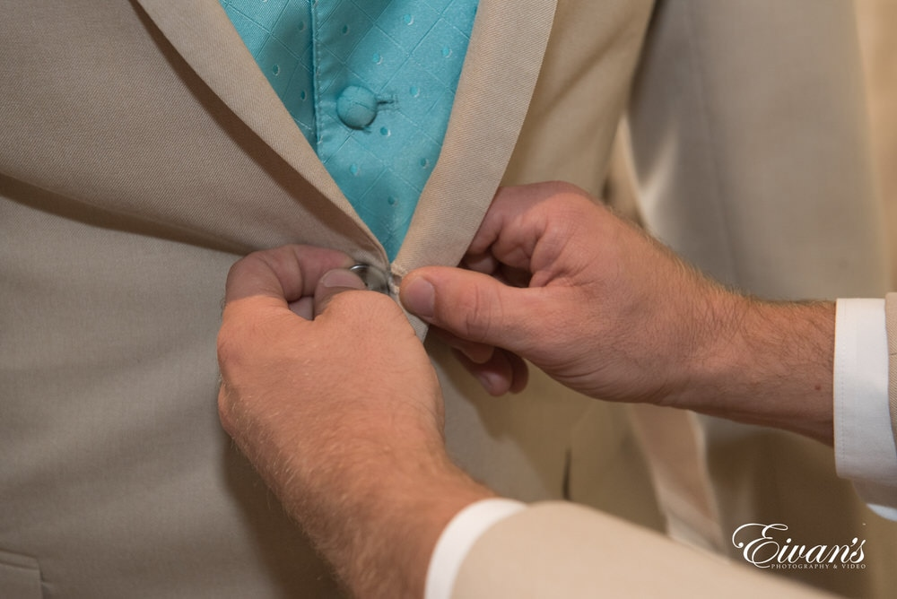 The groom has help with the buttons on his suit jacket.