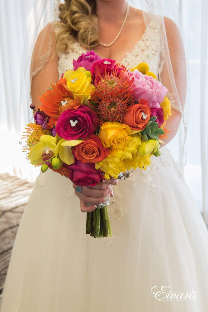 The bride holds her extremely vibrant bouquet with small Mickey mouse adornment