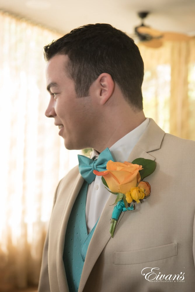 The groom looks off to the right while having his bright orange rose boutonniere.