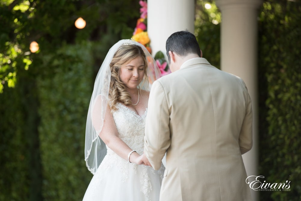 The bride and groom hold hands while their ceremony transcends effortlessly.