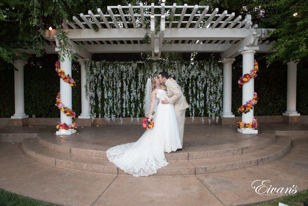 The bride and groom kiss at the top of the alter under an amazing decorative arch.