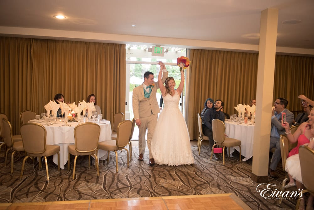 The couple cheer rapidly as they enter their reception to celebrate this perfect day.