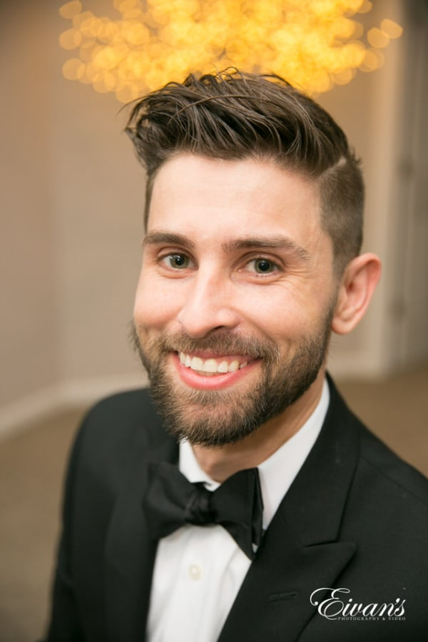 The groom smiles wide for a portrait.
