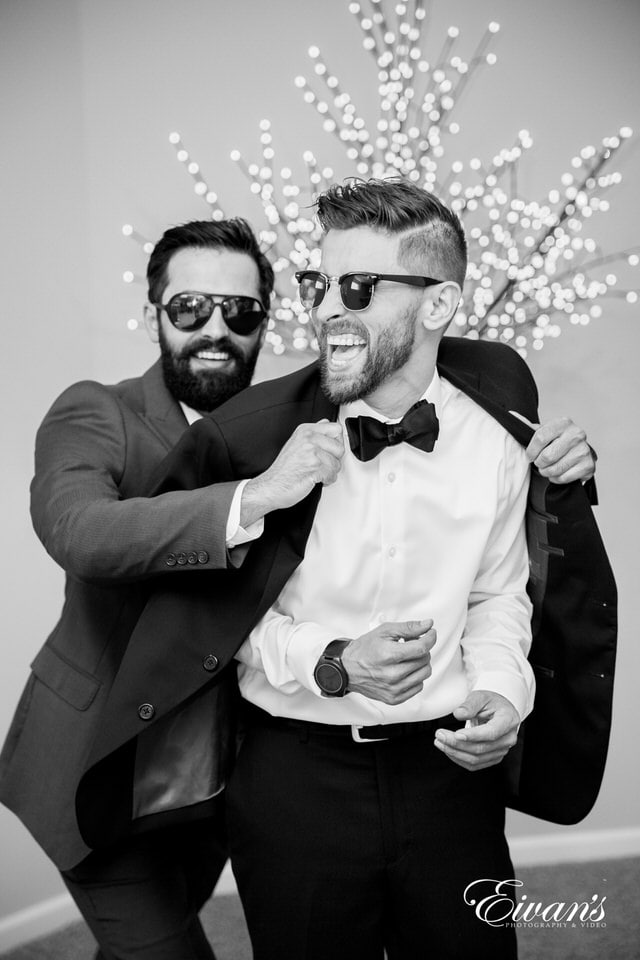 Black and white photo of a groom laughing with his groomsman as he shrugs into his tuxedo jacket.