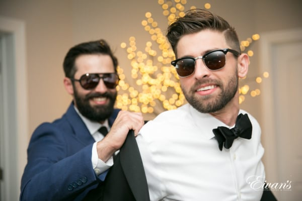 The groom gets help putting his tuxedo jacket on by his groomsman. They both sport dark sunglasses and kind smiles.