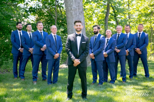 A groom stands, smiling with his arms crossed at the wrist in a forest-like area. His groomsmen flank him on either side in a diagonally increasing line with arms crossed at the wrist.