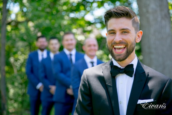 A groom smiles broadly in depth in field shot.