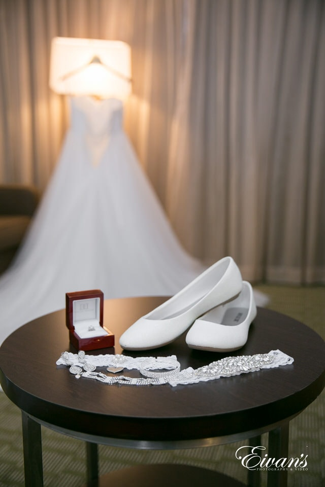 The photographer focuses the camera lens on the bride's shoes, garter, bracelet and weddings ring in a depth of field shot.