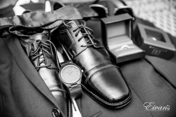 The photographer captures a detail shot of the groom's suit, shoes, watch, sunglasses, bowtie, and rings.