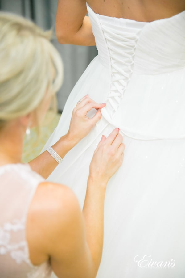 The mother of a bride carefully laces up her daughter's wedding dress.
