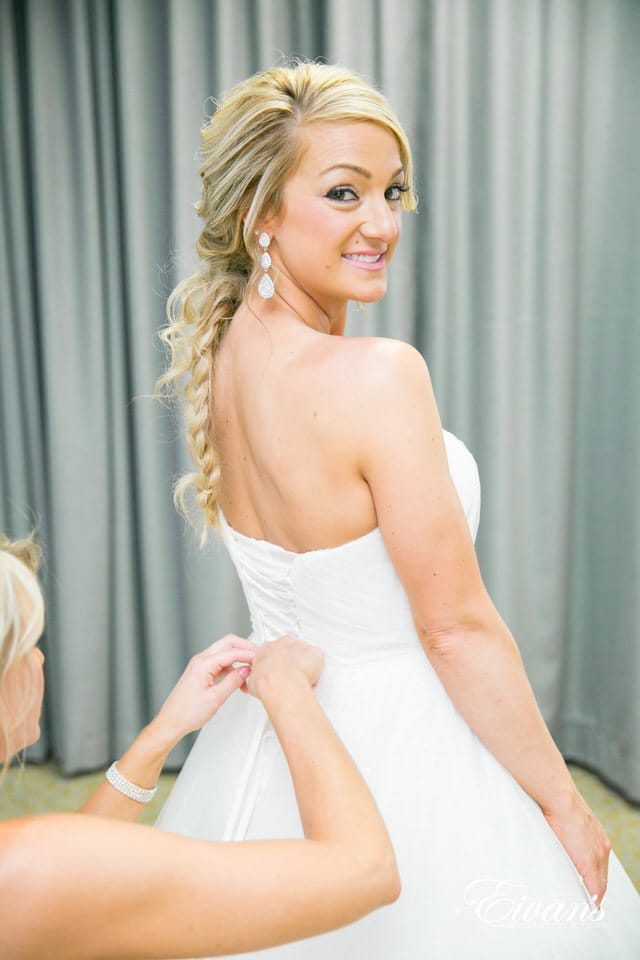 A happy bride looks over her shoulder at the photographer. Her smile is broad and highlighted with pink lips and 3 tier drop earrings. Her blonde hair is tangled in a loose fishtail braid with escaping tendrils. One of her bridesmaids is carefully lacing up the back of her wedding dress.