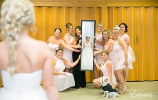 The photographer captures a reflective photo of a bride smiling and looking into a rectangular mirror held by her excited bridal party. Her small, tuxedo-clad dog sits sweetly alongside the bridesmaids.