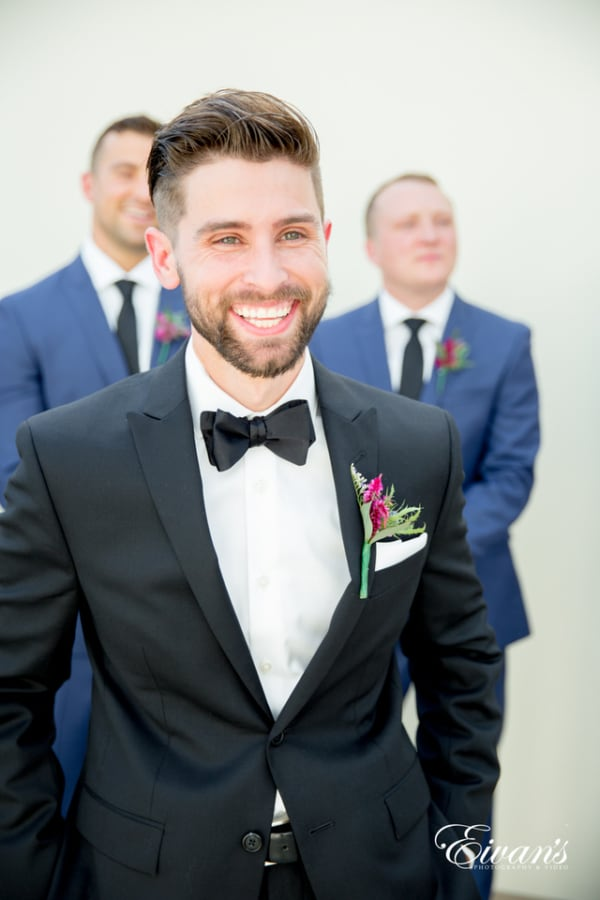 A groom smiles widely for the photographer as his groomsmen stand smiling behind him. The groom wears a black satin bowtie and a wildflower boutonniere.