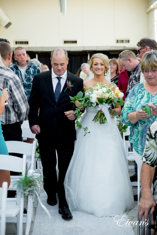 A bride smiles widely as her father walks her down the aisle while guests prepare their phone cameras to take pictures.