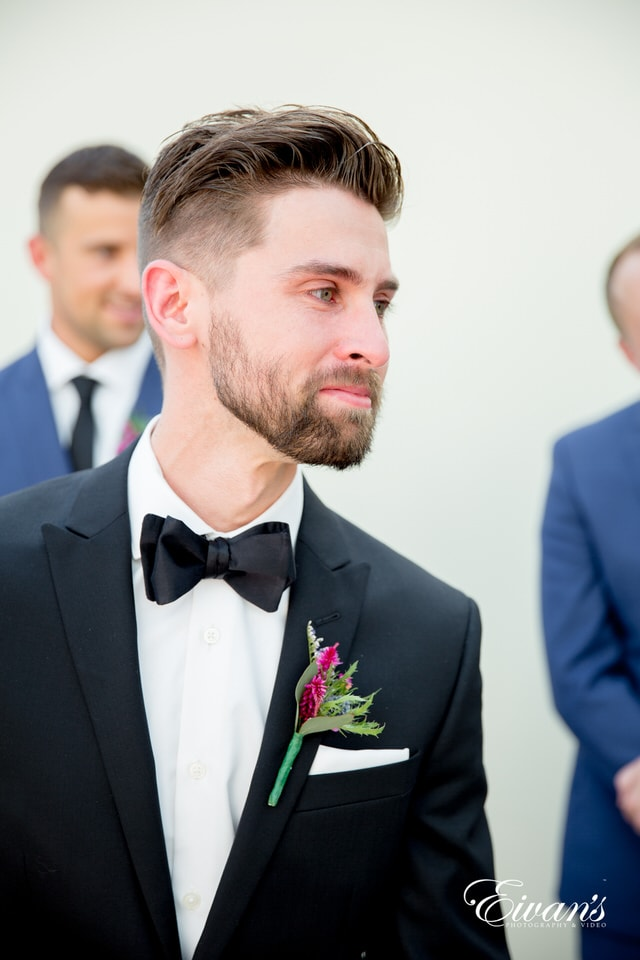 A groom is emotional after his wedding ceremony. He wears a black satin bowtie and a wildflower a boutonniere.