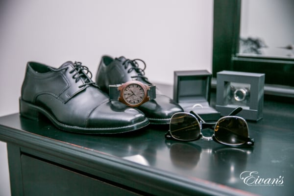 The photographer captures a detail shot of the groom's shoes, watch, sunglasses and rings as they sit on the corner of a dresser.