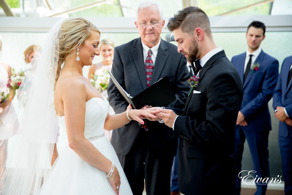 A groom concentrates on putting the wedding band on his bride's finger during their wedding ceremony as the officiant, and bridal party eagerly watch. The bride smiles as she watches her groom slide the ring on her finger.