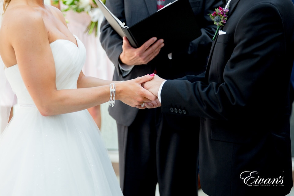 The photographer focuses on the hands of bride and groom during their ceremony as the officiant reads behind them.