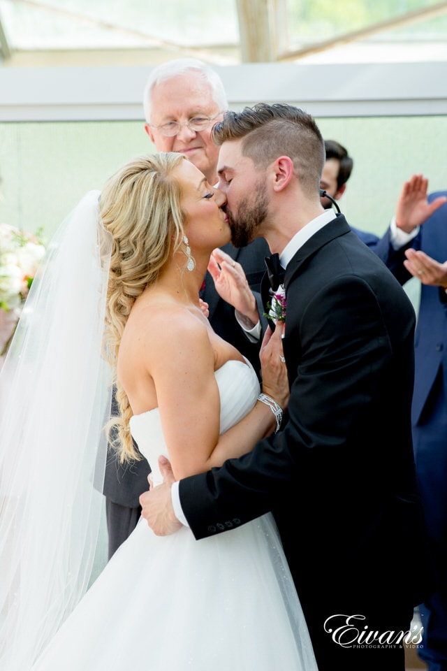 A bride and groom have their first kiss as man and wife at the end of their ceremony. The officiant smiles subtly, and surrounding guests stand and clap.