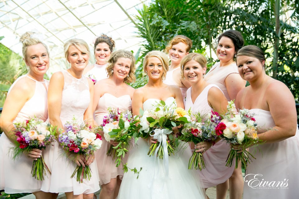 A bride smiles widely, flanked by her bridesmaids with their bouquets in hand. Greenery and tall trees surround the group inside of a high-ceiling glass shelter.