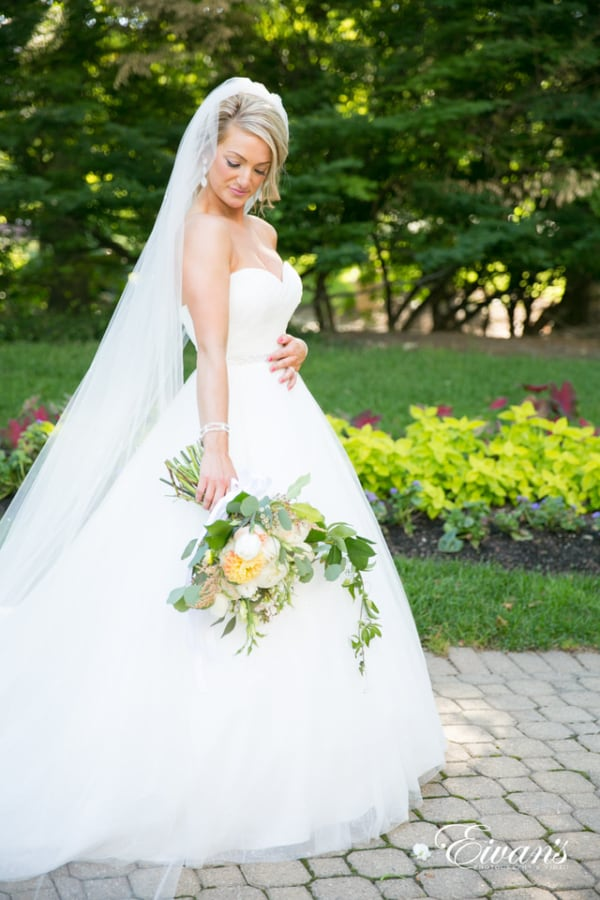 A bride admires her bouquet while walking through the garden wearing a floor-length veil.