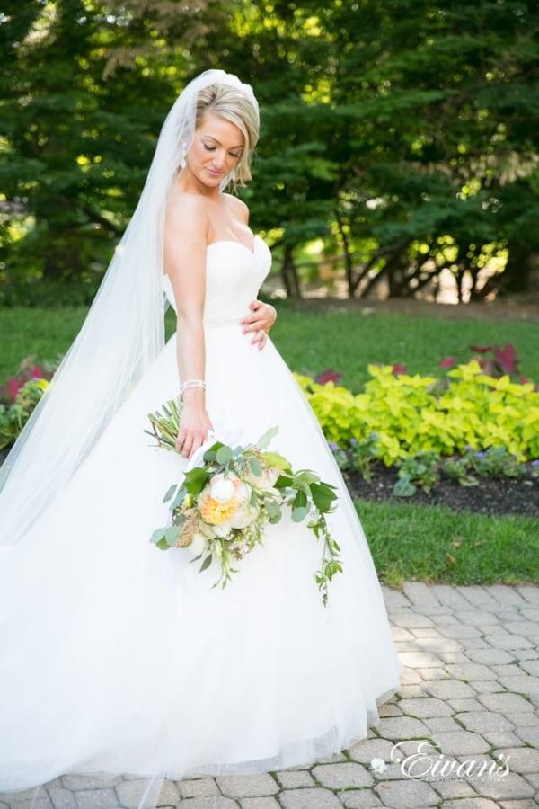 A bride admires her bouquet while walking through the garden wearing a floor-length veil.