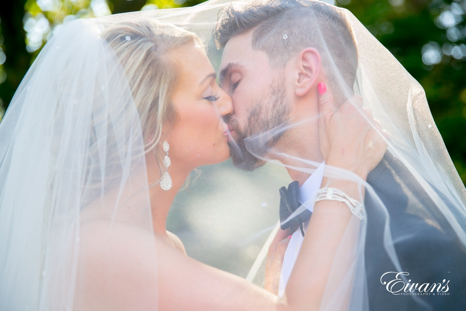 A bride and groom kiss under the cover of the bride's veil.