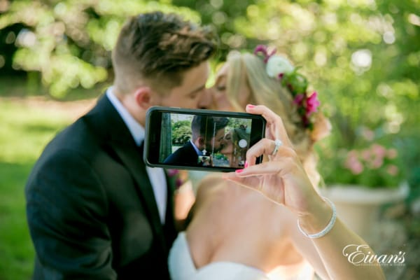 The photographer takes a portrait of a bride snapping a selfie of her and her new husband sharing a kiss.
