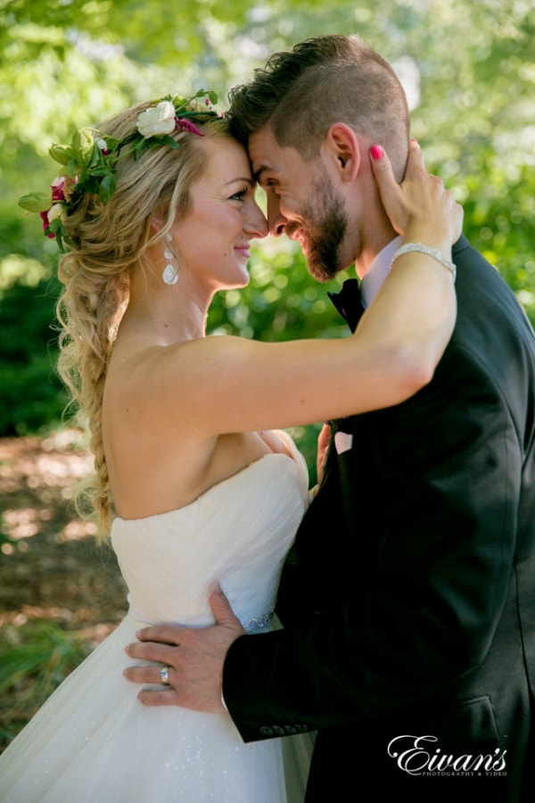A closeup shot of bride and groom looking into each other's eyes in a wooded area.