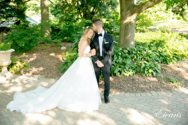 A bride and groom stand in a garden area as they pose for portraits. The groom kisses the forehead of his bride as she rests her head on his shoulder.
