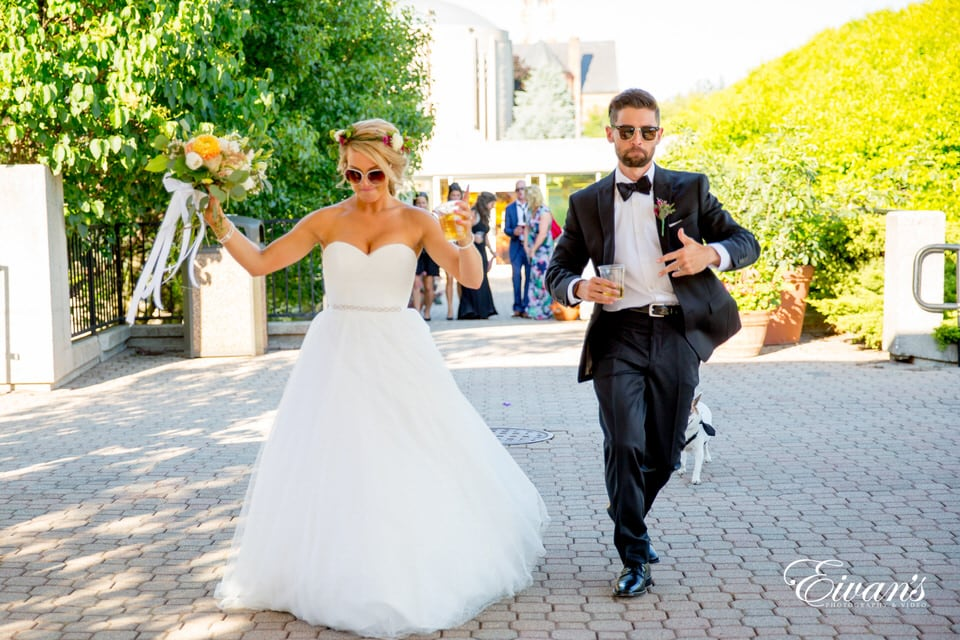 The bride and groom playfully walk toward the photographer as their little dog trails behind them wearing sunglasses with drinks in hand.