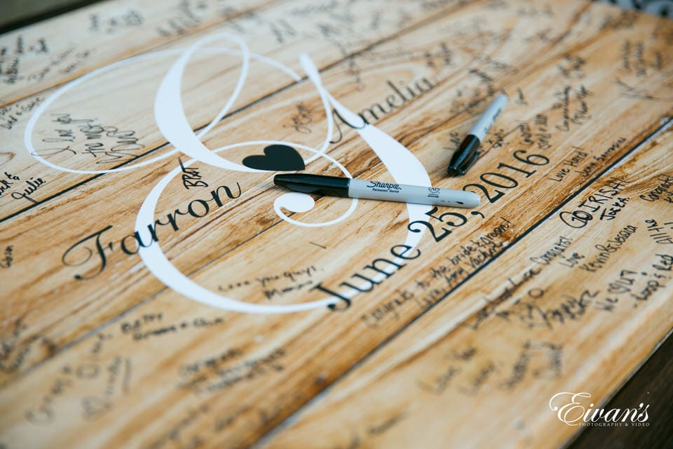 A detail wedding shot of the couple's names and wedding date on a large wooden poster decorated with the names and funny messages of their many guests.