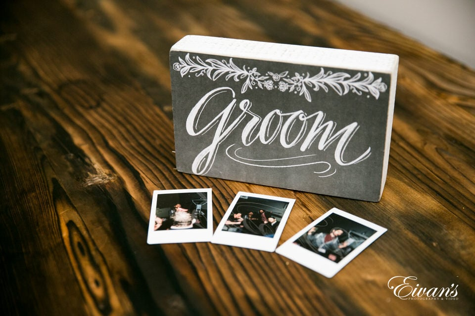 """A small, decorative block with the word """"groom"""" printed on the front rests atop a vintage wood table. Three small polaroid photos lay in front of it."""