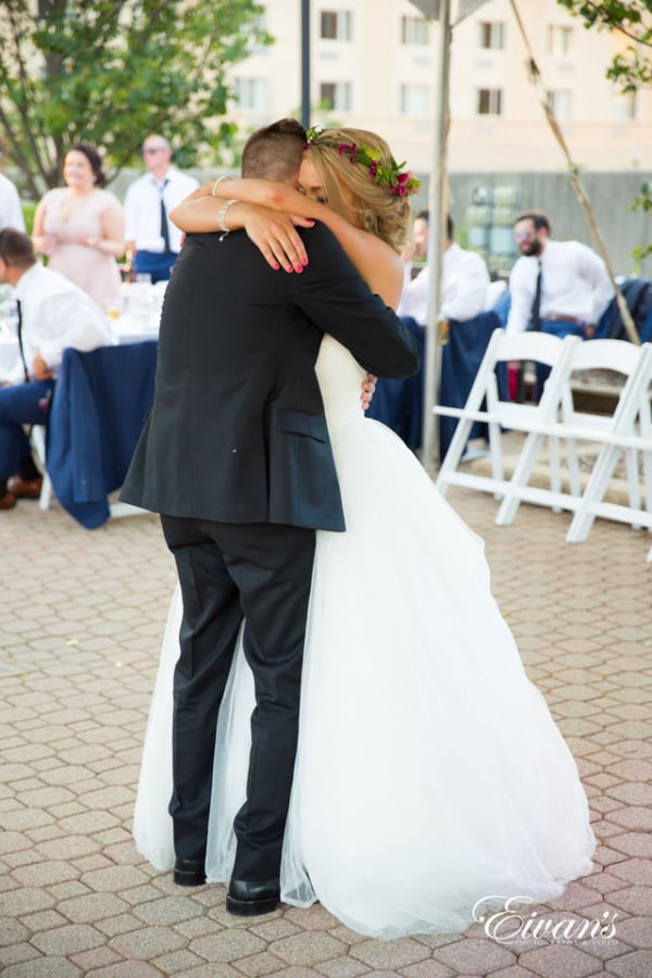 A bride and groom envelop in a tight hug during a dance at their reception.