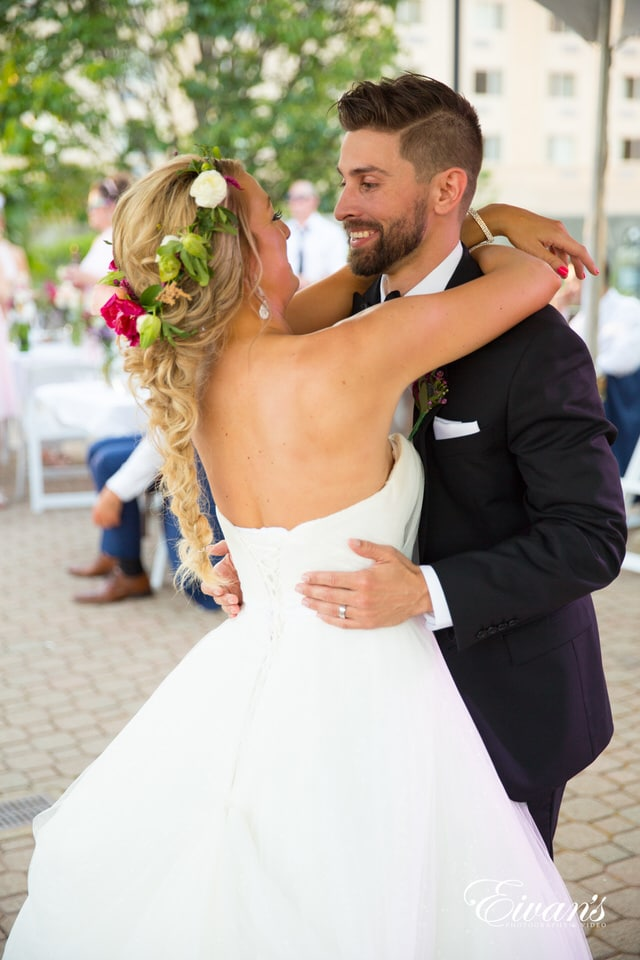 The groom smiles at his new wife as they dance together in a courtyard with their guests lingering in the background. The bride wears a simple hot pink, green and ivory floral crown.
