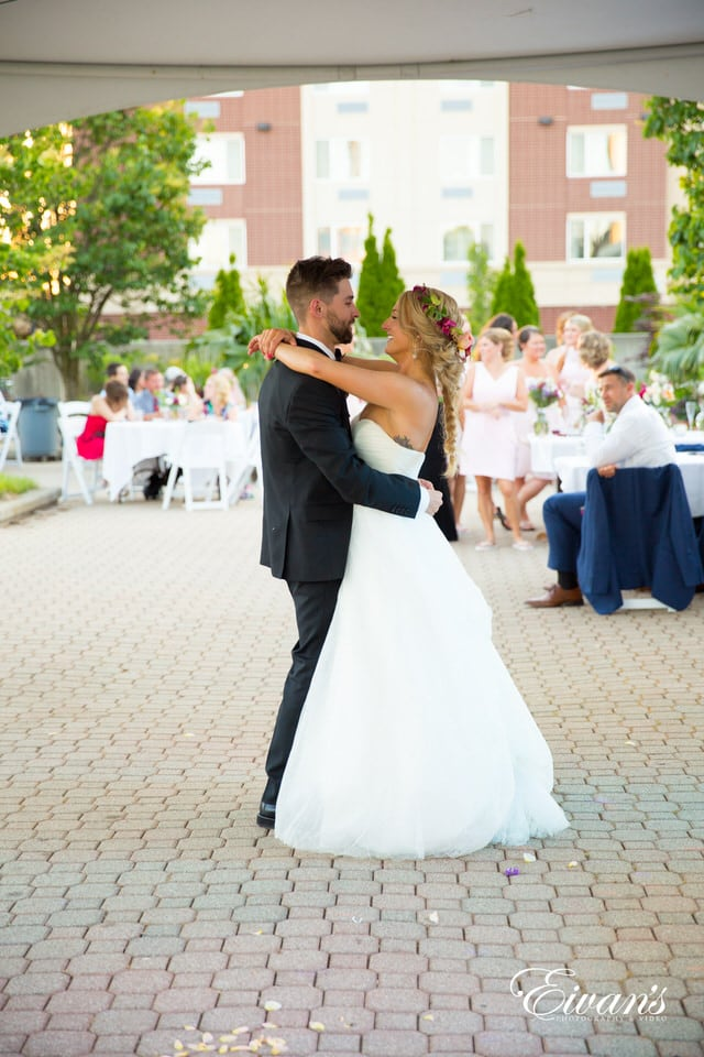 The bride and groom dance chest to chest while smiling at each other during their reception. The bridal party lingers in the background with the rest of the guests.