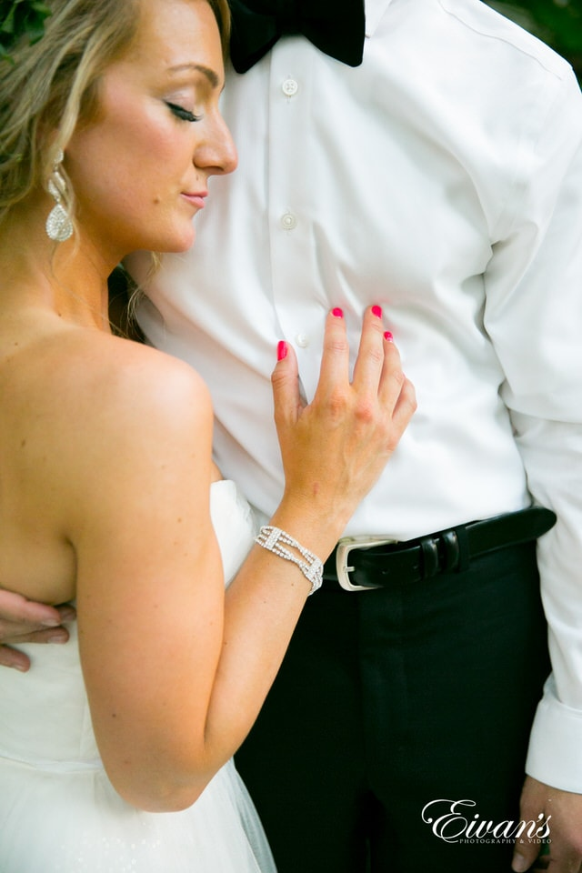 The groom embraces his bride as she stands, resting her head against his chest. The bride sports hot pink nails and silver, jeweled jewelry.